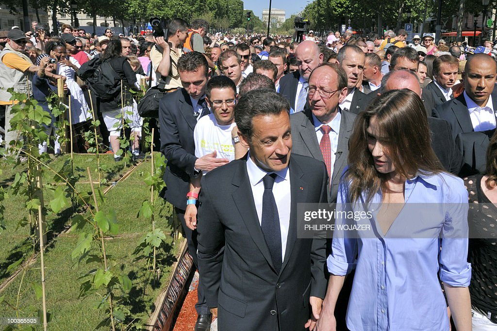 French President Nicolas Sarkozy (L) and his wife Carla Bruni-Sarkozy (R) walk among the crowd as they visit exhibitions on the Champs-Elysees in Paris, on May 24, 2010. The young French farmers' union organized a two-day event called 'Nature Capitale' where they installed the fields and forest of France in the French capital. The union, representing farmers under the age of 35, aim to showcase farm production from sheep breeding to crop growing and win public support for their embattled sector.
