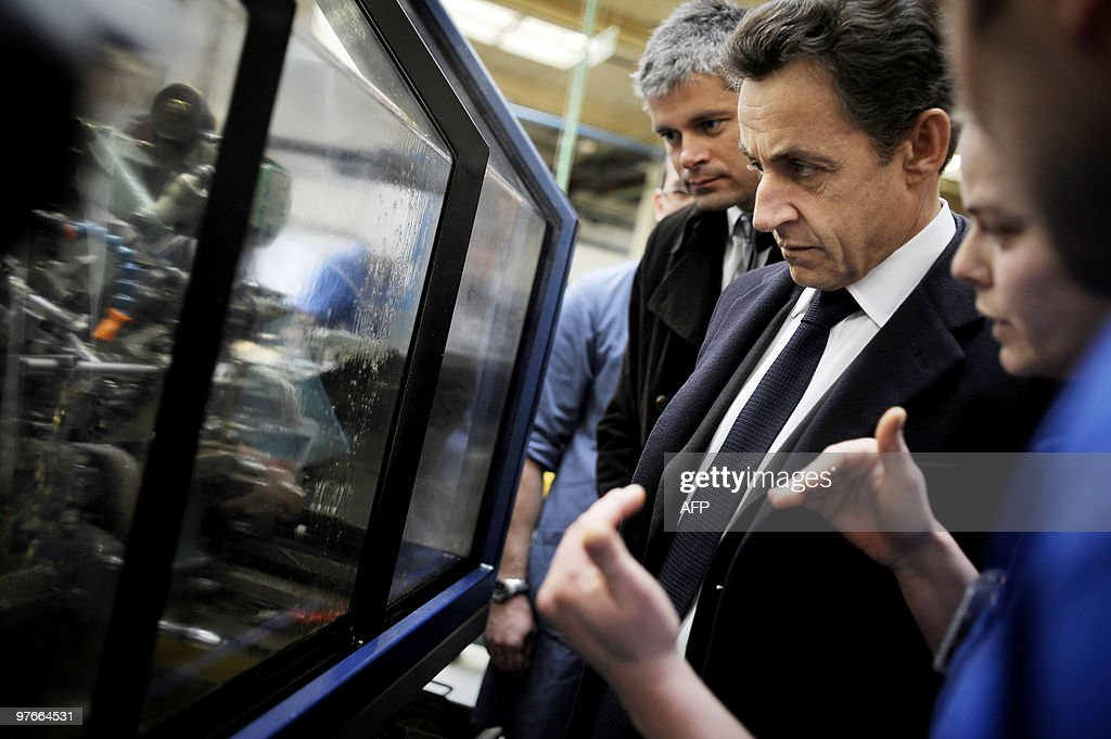 French President Nicolas Sarkozy (C), flanked by Laurent Wauquiez (R), Junior Minister for Employment, speaks with workers, on March 9, 2010 in Pontarlier, eastern France, in the French tyre and valve manufacturer Schrader, during a visit dedicated to employment and professional training.
