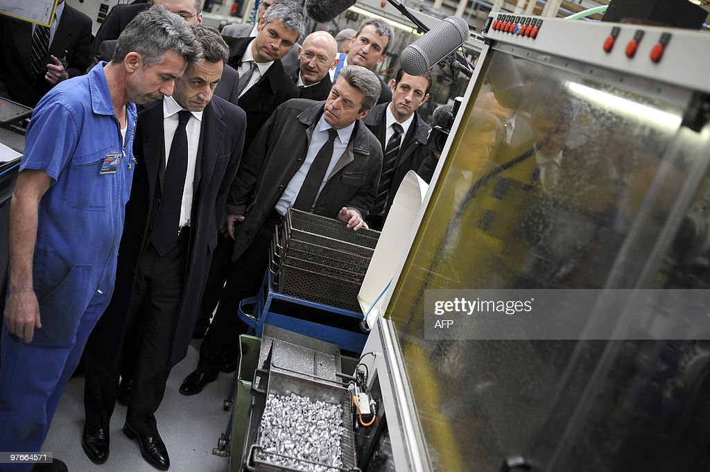 French President Nicolas Sarkozy (2ndL), flanked by Laurent Wauquiez (3rdL), Junior Minister for Employment, and Secretary of State for Cooperation and Francophone Affairs Alain Joyandet (C), speaks with a worker, on March 9, 2010 in Pontarlier, eastern France, in the French tyre and valve manufacturer listens to workers' explanations, on March 9, 2010 in Pontarlier, eastern France, in the French tyre and valve manufacturer Schrader, during a visit dedicated to employment and professional training. Joyandet heads the UMP right-wing ruling party UMP's list for the upcoming French regional elections in Franche-Comte region (eastern France).