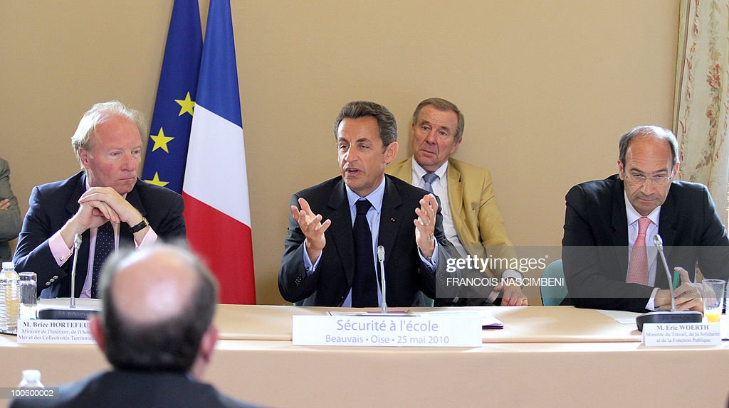 French President Nicolas Sarkozy (C) gives a speech during a meeting on school violences and truancy as French Interior minister Brice Hortefeux (L) and French Labour, Social Relations and Solidarity minister Eric Woerth (R) listen on May 25, 2010 in Beauvais, northern France.
