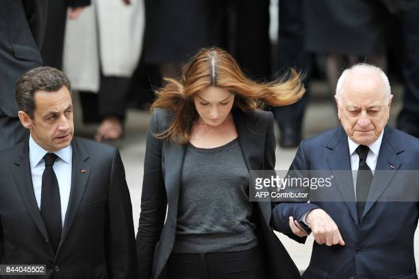 French President Nicolas Sarkozy his wife Carla BruniSarkozy and Pierre Berge the partner of fashion designer Yves SaintLaurent leave the SaintRoch...