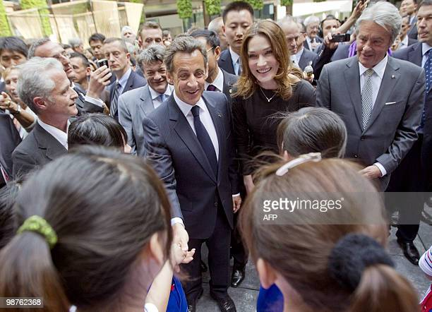 French President Nicolas Sarkozy his wife Carla BruniSarkozy and French actor Alain Delon are greeted by girls as they walk in the French pavilion...