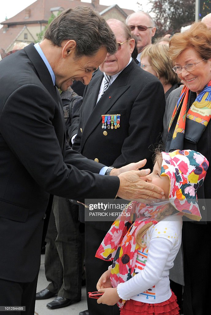 French President Nicolas Sarkozy jokes with a little girl at the end of a ceremony marking the 65th anniversary of the Allied victory over Nazi Germany in World War II, in Colmar, eastern France, on May 8, 2010. French General de Lattre de Tassigny led the French first Army who freed Colmar, on February 2, 1945.