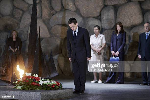 French President Nicolas Sarkozy pays respect after laying a wreath by the eternal flame at the Hall of Remembrance as Former French Minister and...