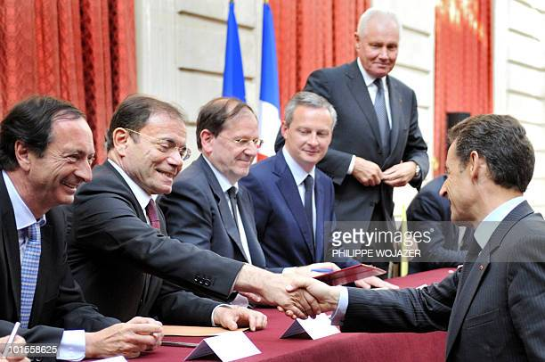 French President Nicolas Sarkozy shakes hands with Casino hypermarket group president JeanCharles Naouri beside French Leclerc hypermarket chain...