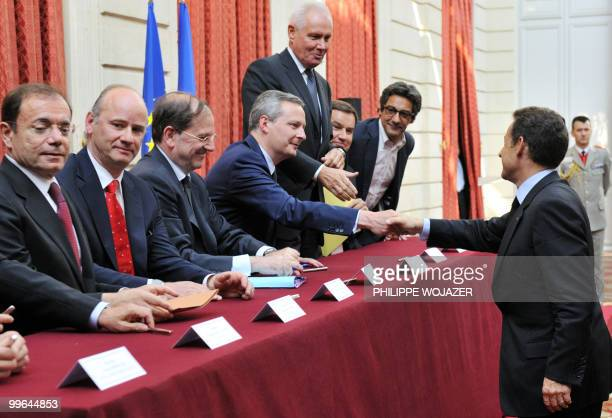French President Nicolas Sarkozy shakes hands with French Agriculture Minister Bruno Le Maire beside Casino hypermarket group president JeanCharles...