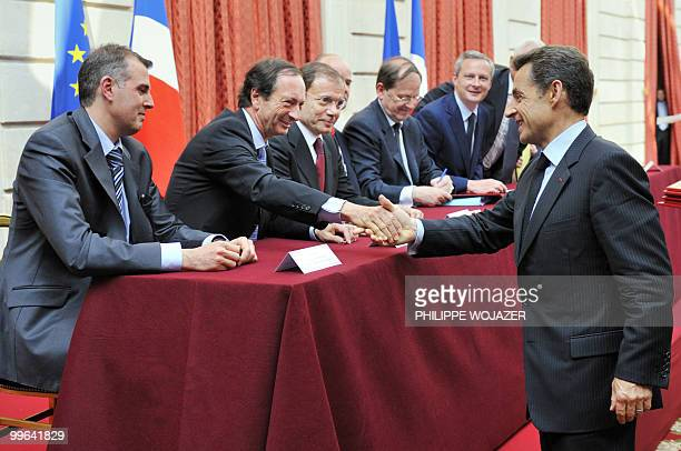 French President Nicolas Sarkozy shakes hands with French Leclerc hypermarket chain president MichelEdouard Leclerc beside Intermarche hypermarket...