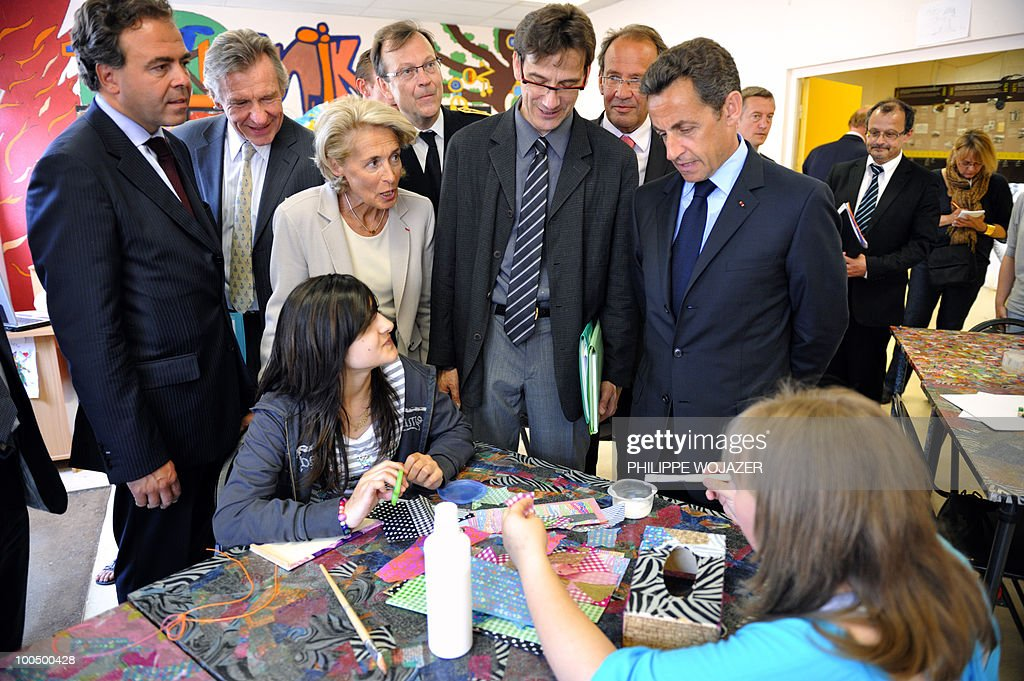 French President Nicolas Sarkozy (R) speaks with pupils as he visits a classroom at the Charles Fauqueux college with French Education minister Luc Chatel (L) after a meeting on school violences and truancy, on May 25, 2010 in Beauvais, northern France.