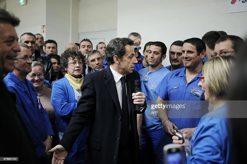 French President Nicolas Sarkozy (C) speaks with workers of the Schrader's factory on March 9, 2010 in Pontarlier, eastern France, during a visit dedicated to employment and professional training.