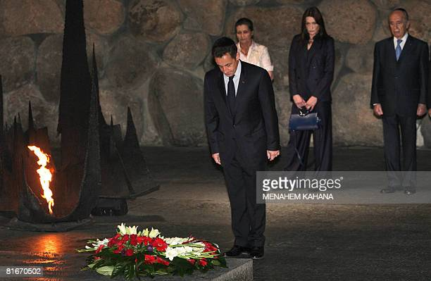 French President Nicolas Sarkozy stands near the eternal flame watched by his wife Carla French philosopher and Holocaust survivor Simone Weil and...