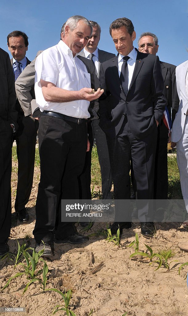 French President Nicolas Sarkozy (R) watches farmer Philippe Blouin (L) showing him his plantation, on May 21, 2010 in Bouglon, southwestern France, during his visit with French Agriculture Minister Bruno Le Maire (C).