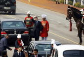 French President Nicolas Sarkozy wave as he leaves Vijay Chowk after watching India's 59th Republic Day parade from a bulletproof box in New Delhi 26...
