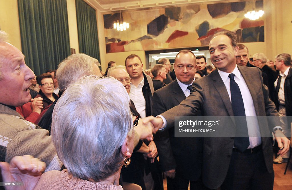 French President of the Union for a Popular Movement right-wing opposition party (UMP) Jean-Francois Cope (R) shakes hands with supporters before a meeting at the City Hall of Chartres, central France, on December 10, 2012. AFP PHOTO / MEHDI FEDOUACH