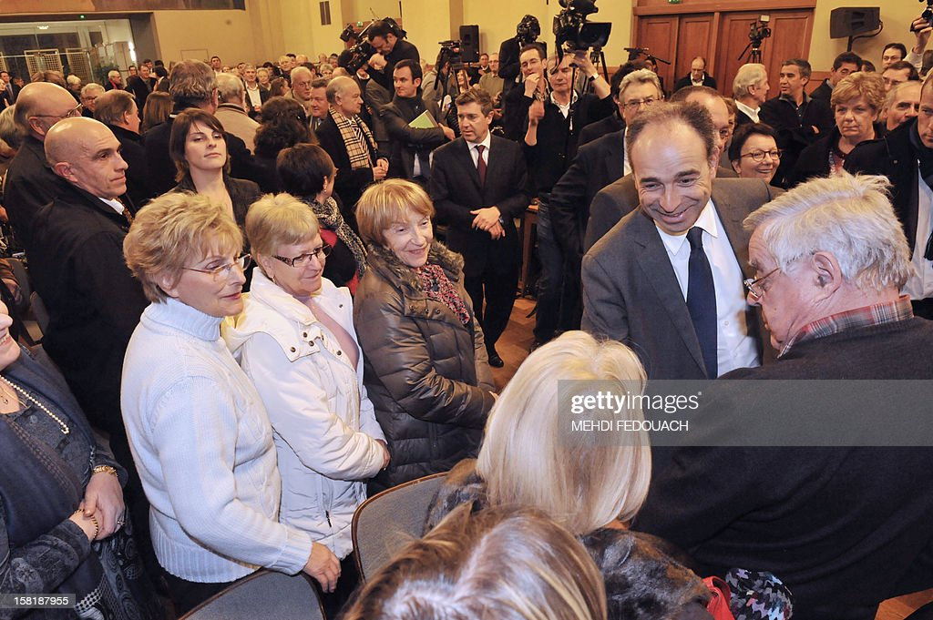 French President of the Union for a Popular Movement right-wing opposition party (UMP) Jean-Francois Cope (2nd-R) shakes hands with supporters before a meeting at the City Hall of Chartres, central France, on December 10, 2012.