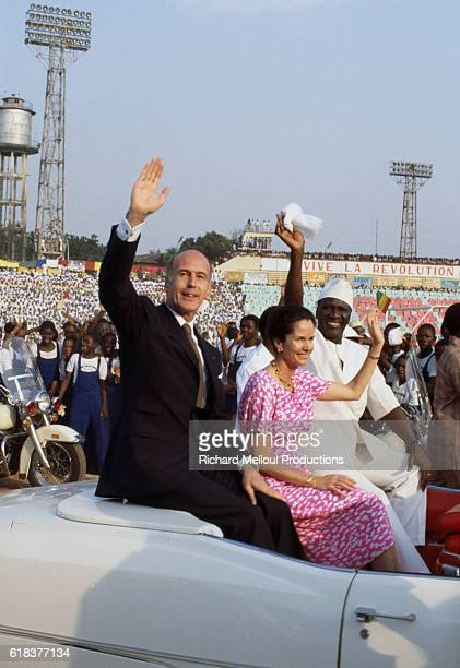 French President Valery Giscard d'Estaing and his wife First Lady AnneAymone Giscard d'Estaing wave to supporters during an official visit to Guinea...