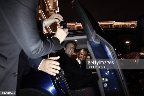 French presidentelect Emmanuel Macron and his wife Brigitte Trogneux sit in a car at the Louvre Museum in Paris on May 7 after the second round of...