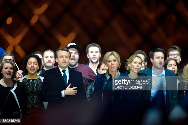 French presidentelect Emmanuel Macron and his wife Brigitte Trogneux sing the national anthem with supporters in front of the Pyramid at the Louvre...
