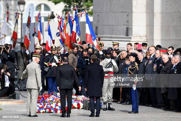 French presidentelect Emmanuel Macron and outgoing French President Francois Hollande pat their respects as they attend a ceremony to mark the...
