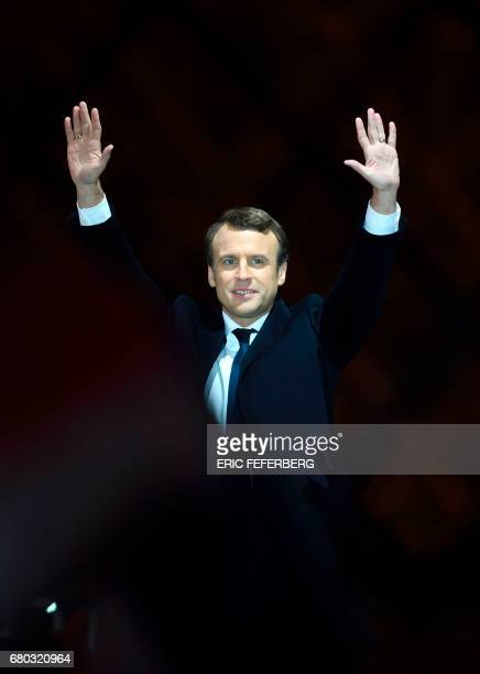 French presidentelect Emmanuel Macron greets supporters as he arrives to deliver a speech in front of the Pyramid at the Louvre Museum in Paris on...