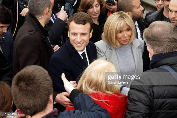French presidential candidate Emmanuel Macron for the En Marche movement flanked by his wife Brigitte Trogneux speaks with supporters as he leaves...