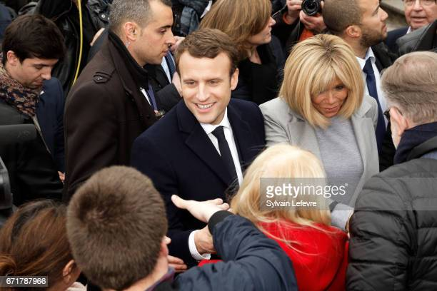 French presidential candidate Emmanuel Macron for the En Marche movement flanked by his wife Brigitte Trogneux speak with supporters as he leaves the...