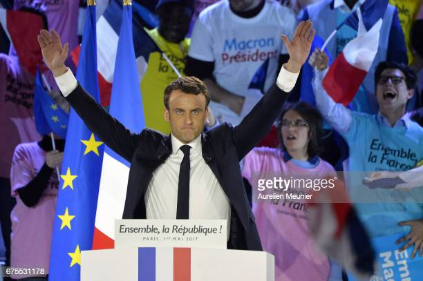 French Presidential Candidate Emmanuel Macron salutes voters as he arrives for a political meeting at Grande Halle de La Villette on May 1 2017 in...