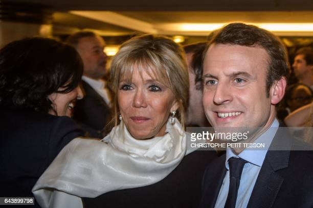 French presidential election candidate for the 'En Marche' movement Emmanuel Macron and his wife Brigitte Trogneux pose prior to the 32nd annual...