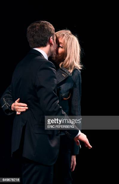 French presidential election candidate for the En Marche movement Emmanuel Macron and his wife Brigitte Trogneux kiss as they attend an event...