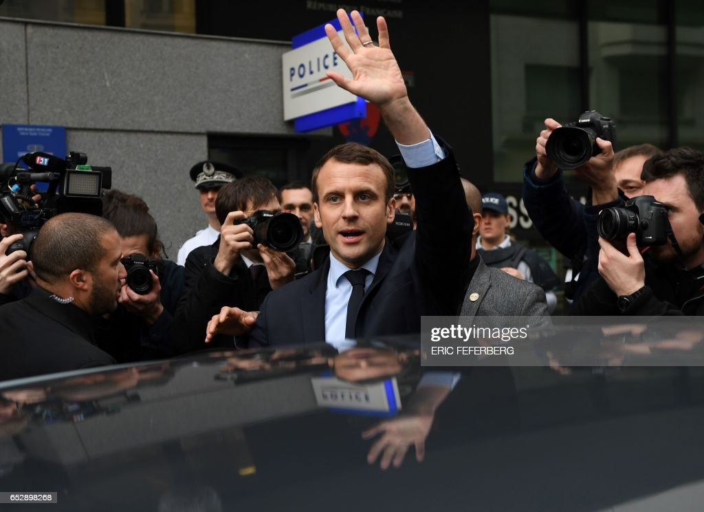 French presidential election candidate for the En Marche ! movement Emmanuel Macron gestures as he leaves after paying a visit to the local police station in the 20th arrondissement of Paris on March 13, 2017. / AFP PHOTO / Eric FEFERBERG