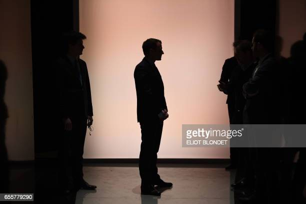 French presidential election candidate for the En Marche movement leader Emmanuel Macron stands before a debate organised by the French private TV...