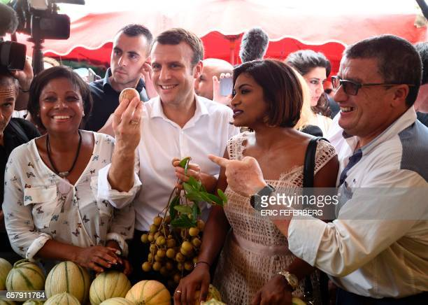 French presidential election candidate for the En Marche movement Emmanuel Macron flanked by member of the National Assembly Monique Orphe holds a...