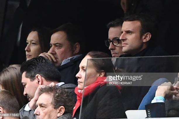 French presidential election candidate for the En Marche movement Emmanuel Macron and his spokesperson Laurence Haim attend the French L1 football...