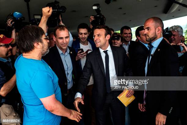French presidential election candidate for the En Marche movement Emmanuel Macron is about to shake hands with a supporter of French presidential...