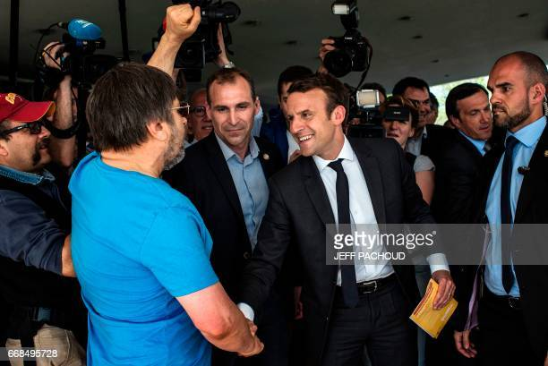French presidential election candidate for the En Marche movement Emmanuel Macron shakes hands with a supporter of French presidential election...