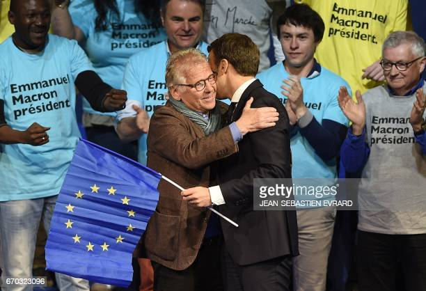 French presidential election candidate for the En Marche movement Emmanuel Macron holds a EU flag as he arrives on stage and salutes French and...