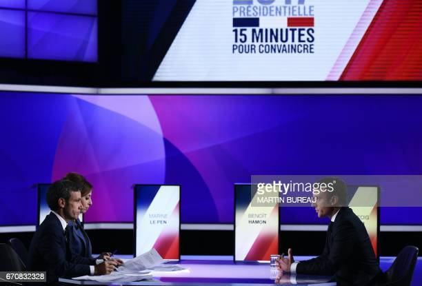 French presidential election candidate for the En Marche movement Emmanuel Macron speaks with French journalists and television hosts David Pujadas...