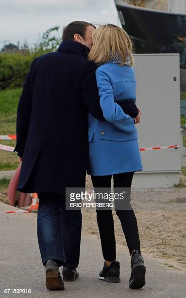 French presidential election candidate for the En Marche movement Emmanuel Macron and his wife Brigitte Trogneux kiss as they pose for the photograph...