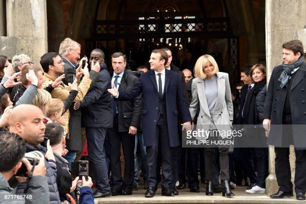 French presidential election candidate for the En Marche movement Emmanuel Macron speaks with supporters as he leaves with his wife Brigitte Trogneux...