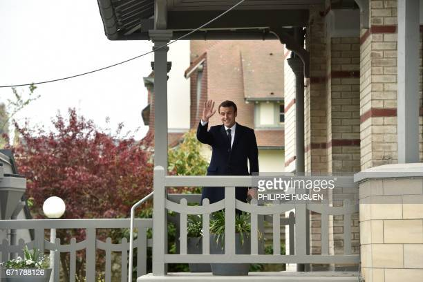 French presidential election candidate for the En Marche movement Emmanuel Macron waves at supporters outside his house after voting in Le Touquet...