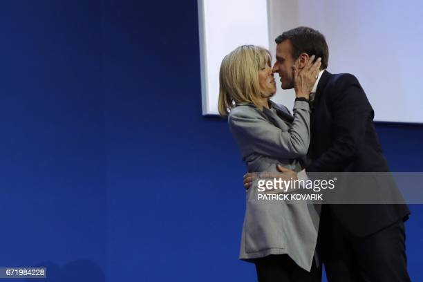 French presidential election candidate for the En Marche movement Emmanuel Macron kisses his wife Brigitte Trogneux prior to deliver a speech at the...