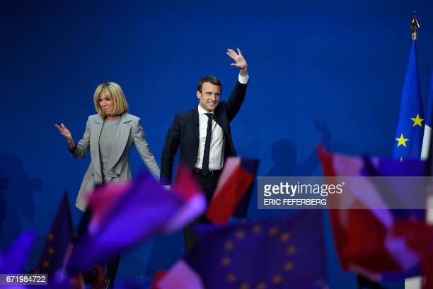 TOPSHOT French presidential election candidate for the En Marche movement Emmanuel Macron and his wife Brigitte Trogneux arrive on stage at the Parc...