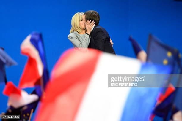TOPSHOT French presidential election candidate for the En Marche movement Emmanuel Macron kisses his wife Brigitte Trogneux on stage at the Parc des...