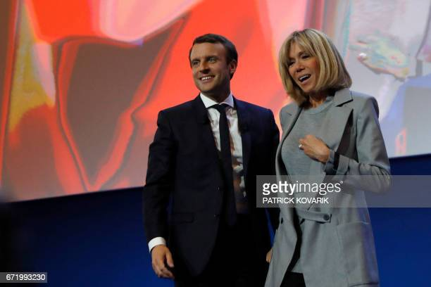 French presidential election candidate for the En Marche movement Emmanuel Macron and his wife Brigitte Trogneux react during a meeting at the Parc...