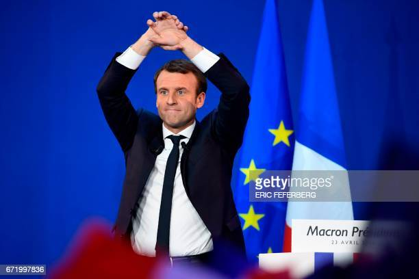TOPSHOT French presidential election candidate for the En Marche movement Emmanuel Macron raises the arms at the Parc des Expositions in Paris on...