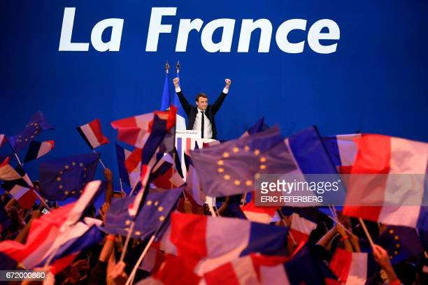 TOPSHOT French presidential election candidate for the En Marche movement Emmanuel Macron waves at the audience during a meeting at the Parc des...