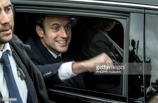 TOPSHOT French presidential election candidate for the En Marche movement Emmanuel Macron smiles as he leaves after voting at a polling station in Le...