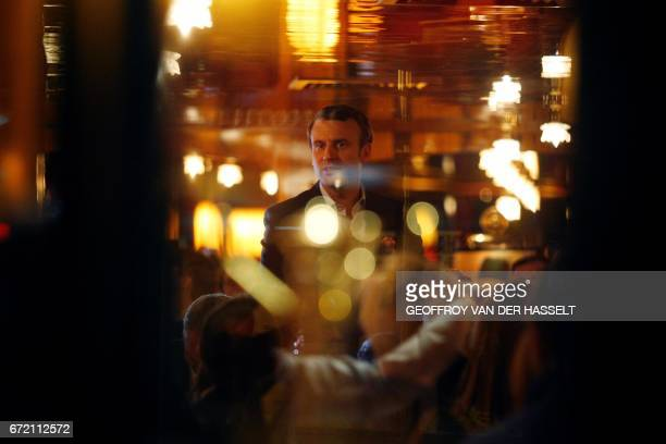 TOPSHOT French presidential election candidate for the En Marche movement Emmanuel Macron looks on at La Rotonde restaurant in Paris on April 23...