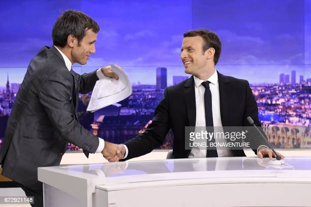 French presidential election candidate for the En Marche movement Emmanuel Macron shakes hands with French journalist David Pujadas before an...