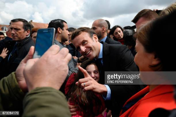 French presidential election candidate for the En Marche movement Emmanuel Macron poses with a young girl in Amiens on April 26 2017 Macron announced...