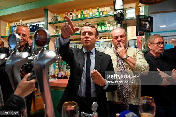 TOPSHOT French presidential election candidate for the En Marche movement Emmanuel Macron gestures from behind the bar counter as he meets with...